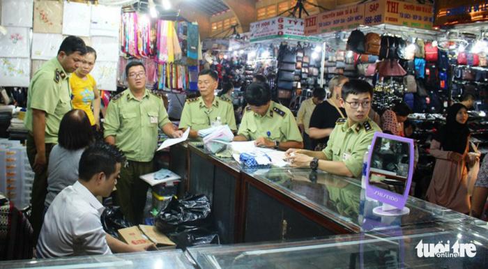 Lực lượng quản lý thị trường kiểm tra hàng giả tại chợ Bến Thành